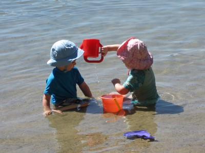 two smallish children playing around the fish bucket