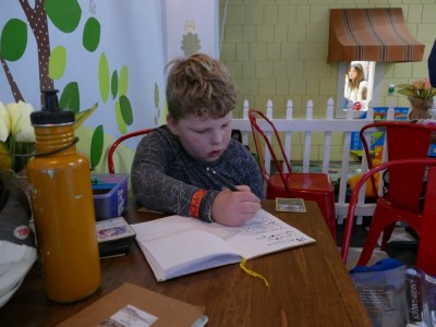 Harvey writing in his notebook homework at the playspace