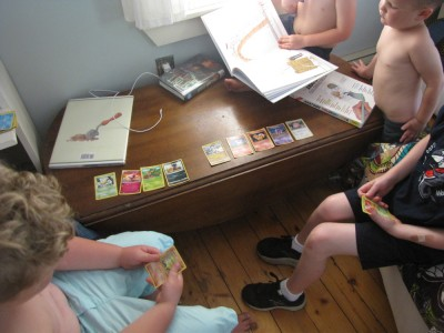 boys and friends playing with pokemon cards