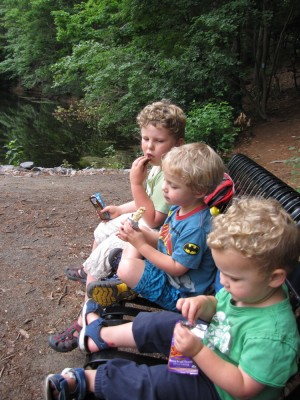 the boys sitting on a bench eating their hiking snack