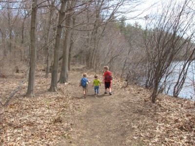 three boys walking together around the pond