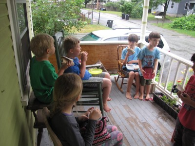 kids eating lunch on the porch on a rainy day