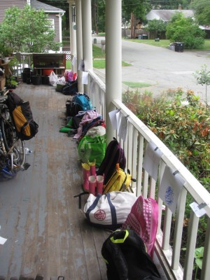 many backpacks lined up along the edge of the porch