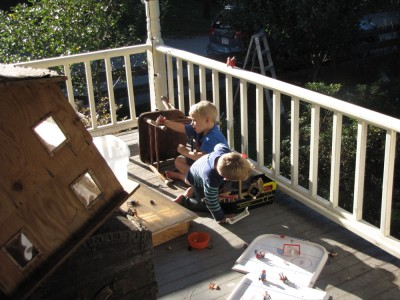Zion and Lijah playing with toys on the porch