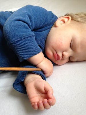 Lijah asleep, clutching his chopstick