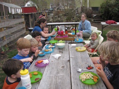 lots of kids and a few adults eating at our picnic tables
