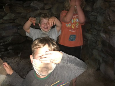 the boys shielding their eyes from the camera flash in a root cellar cave
