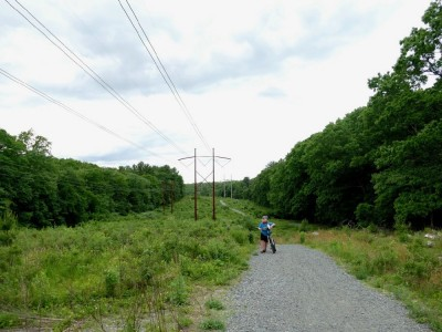 Harvey walking his bike up a steep hill on a path beneath high-tension lines
