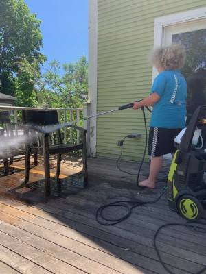 Harvey powerwashing a chair on the back porch