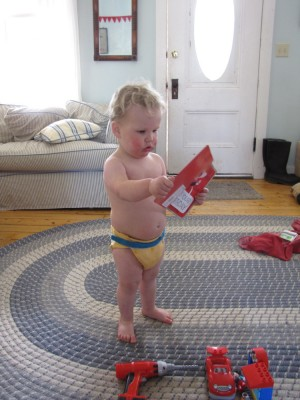 Lijah in just a diaper looking at a birthday card, new toys at his feet