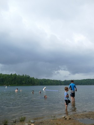 the kids in the water at Walden Pond under ominous gray clouds