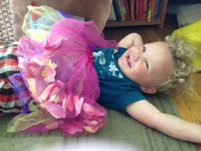 Lijah lying down wearing a pink and purple tutu over his clothes