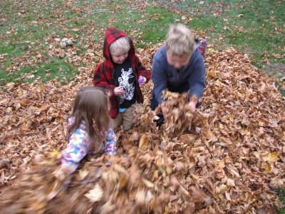 Harvey, Zion, and Taya digging for prizes in the leaf pile