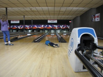Zion lying down to watch his ball hitting the pins