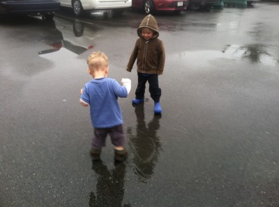 Zion and Lijah looking for puddles in a parking lot
