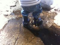 Zion's rain-booted feet splashing in a puddle