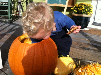Lijah, cookie in his other hand, reaching deep into the pumpkin to pull out some goop