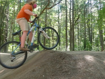 Harvey going over a dirt hill on a pump track