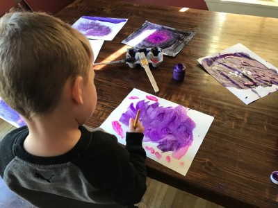 Lijah painting purple art at the kitchen table