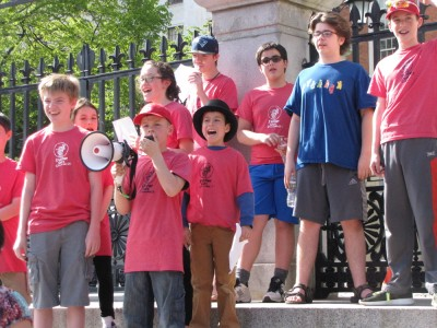 a group of kids in red shirts chanting on the State House steps