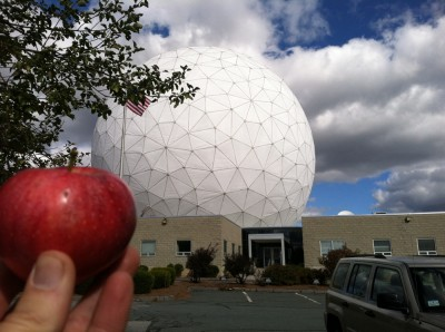 me holding a red apple in front of the Haystack Radio Telescope