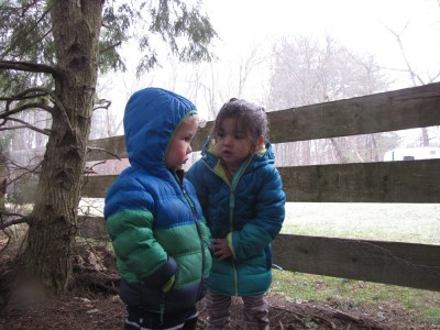 Lijah and a friend playing under the tree on a cold wet day