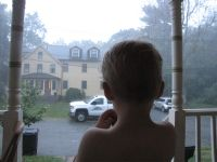 Zion watching late-evening rain from the front porch