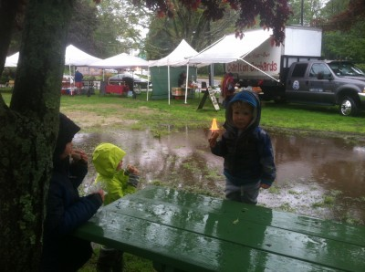 the boys eating donuts by a huge puddle at the farmers market