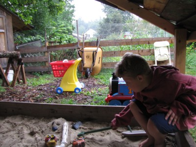 Harvey playing in the sandbox in the rain