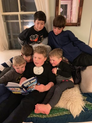 Harvey reading Dog Man to brothers and friends
