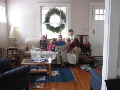 Grandpa reading to Nisia and the boys on his couch