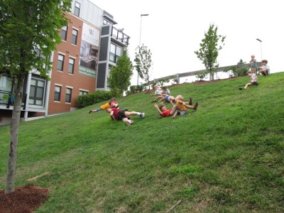kids and a parent rolling down a steep grassy bank
