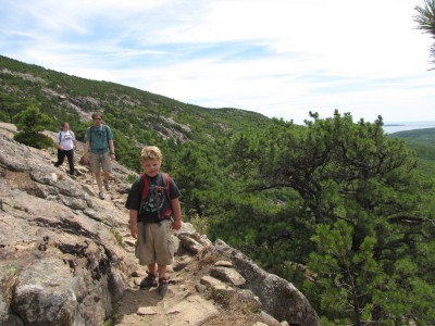 Harvey, Kyle, and Margaret hiking a steep-sided trail on Hugonaut Head