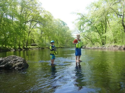Zion and Harvey standing on rocks in the middle of the Assabet River