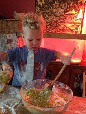 Lijah stirring batter in front of the chicks and their red heat lamp