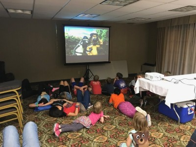 kids watching Shaun the Sheep in a conference room