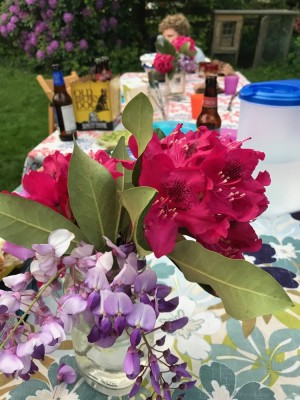 a bouquet of rhododendron and wisteria flowers on the picnic table