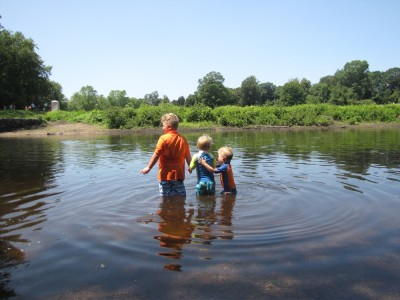 the three boys wading in the river