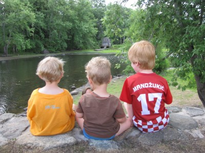 Zion, Lijah, and Nathan sitting on a stone wall above the river