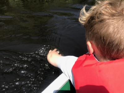 Lijah in the canoe trailing his hand in the water