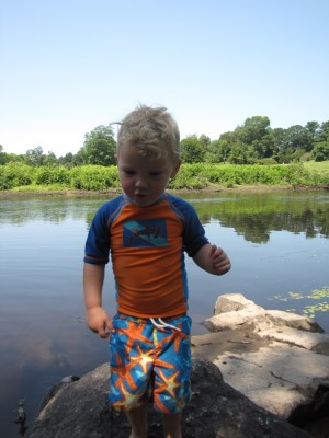 Lijah in his swimsuit on the river bank