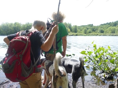 Harvey and Zion, with backpacks and walking sticks, looking at the Concord River