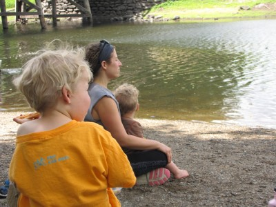 Zion, Mama, and Lijah sitting beside the Concord River