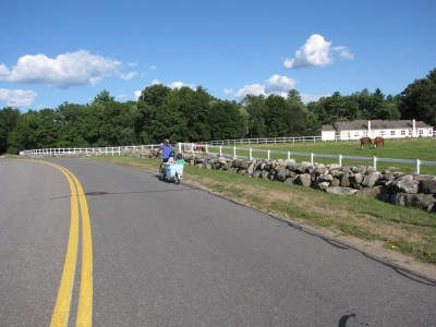 the big bike passing by a sprawling horse farm, with white barns and fences