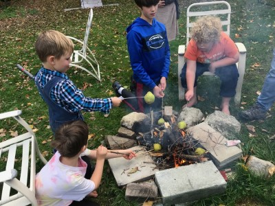 kids roasting pears on sticks over a fire