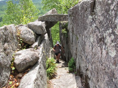 Becca climbing up an exposed path, passing under a block of granite