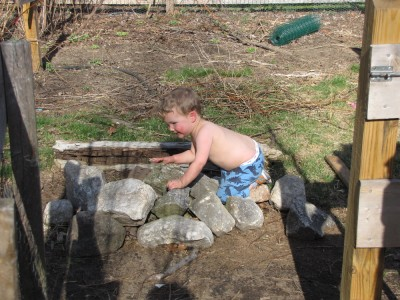 shirtless Lijah playing on a pile of rocks
