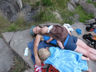 Archibalds sleeping on a shady rock: Zion wrapped in towels, and Leah lying with Lijah in the Ergo