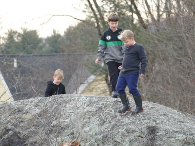 Zion, Lijah, and Matthew atop a big rock by the Lexington bell-tower