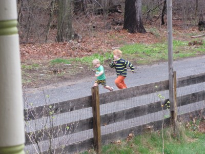Zion and Nathan running on the street, seen from the porch